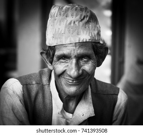 Pokhara, Nepal - Circa September 2017 - A black and white portrait shot of a local Nepalese man wearing a high hat smiling