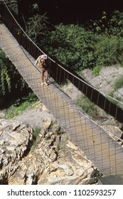 POKHARA, NEPAL - DEC 2, 1987 - Crossing a suspension bridge over the Kali Gandaki river, Himalaya,Nepal