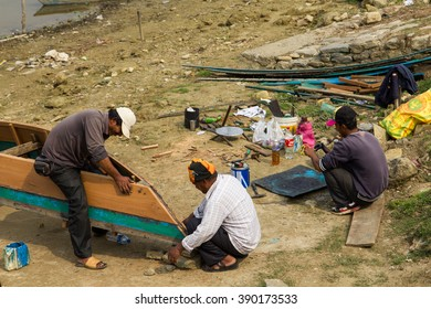 POKHARA, NEPAL - MARCH 12, 2016: Local boatmen repair a wooden boat.