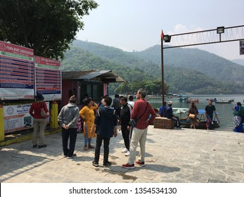 Pokhara / Nepal - March 31 2019: Some tourists waiting for boats at Phewa Lake at a hot afternoon.