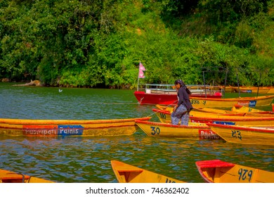 POKHARA, NEPAL - NOVEMBER 04, 2017: Close up up of woman standing over a yellow boat at Begnas lake in Pokhara, Nepal
