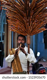 Pokhara / Nepal - November 20 2009: a Nepali man plays a wooden flute as he gracefully balances a wooden tree of flutes for sale to tourists