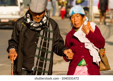 Pokhara, Nepal - November 21, 2015: Elderly couple walking on the street in Pokhara, holding each other's hand.