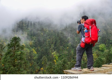Pokhara, Nepal - Oct 22, 2017. Traveler with backpack in mountains enjoying on view of foggy karst mountains.