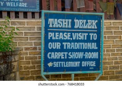POKHARA, NEPAL - OCTOBER 06 2017: Informative sign of tashi delek, to visit the carpet show room in settlement office in Pokhara, Nepal