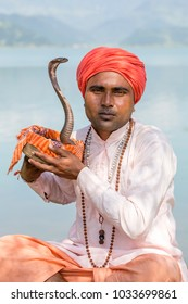 POKHARA, NEPAL - OCTOBER 07, 2016 : Portrait of snake charmer adult man in turban and cobra sitting near the lake in Pokhara, Nepal