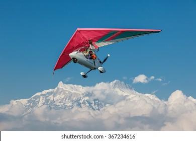 POKHARA, NEPAL - OCTOBER 30, 2009: The motor hang-gliding in the sky near the himalayan peaks Machhapuchre - Annapurna region, Nepal