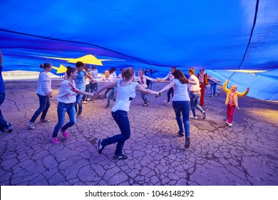 Pokrovsk, Ukraine - May 19, 2016: Celebrating the Day of Europe in the Ukrainian city of Pokrovsk, children dance and take pictures under the huge flag of the European Union. Donetsk region