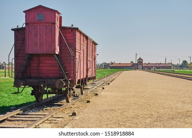 Oświęcim /Poland - 10 August 2019: Auschwitz-Birkenau Memorial and Museum old wooden train wagon on the background of the entrance watch tower.