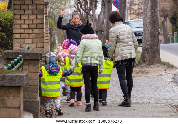 LUBAŃ, POLAND - April, 2019: Group of preschool children dressed in highlight yellow reflective vests to be easily seen by car drivers. Safe kindergarten kids walk in city streets. Road safety concept