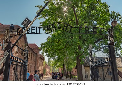"""Poland Auschwitz 19-September -2018 View of the iron gate of the entrance with above the sign """"arbeit macht frei"""" of concentration camp Auschwitz. In the background the stone barracks ."""