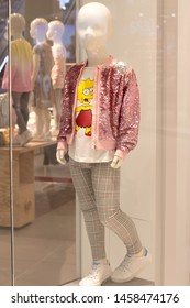 Poland, Bydgoszcz - May 15, 2019: Children's white mannequin girl in a shop window. Dummy dressed in a T-shirt Lisa Simpson, pants and pink jacket with rhinestones. Shopping to school