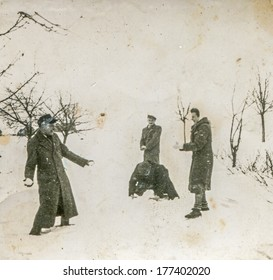POLAND, CIRCA FORTIES - Vintage photo of group of people throwing snowballs in winter
