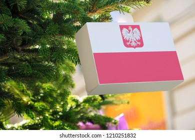 Poland flag with the coat of arms printed on a Christmas gift box. Printed present box decorations on a Xmas tree branch. Christmas shopping in Poland, sale and deals concept.