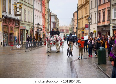 Poland, Krakow, September 14, 2015: Guests of the city, tourists and travelers, townspeople ride on carriages and horses in the ancient Market Square, the main sight of the city