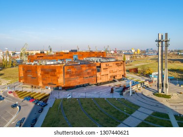 Gdańsk, Poland - October 16, 2018: Rusty steel building of European Solidarity Center and museum in Gdansk and the monument to the Fallen Shipyard Workers of 1970 with three crosses and anchors