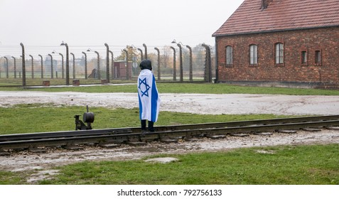 O?wi?cim, Poland - October 22, 2017: An unknown man wearing the flag of Israel standing on the railroad track att the Memorial and museum Auschwitz-Birkenau, former German Nazi concentration and exter