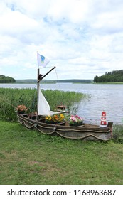 POLAND, PODLASKIE VOIVODESHIP, AUGUSTOW COUNTY, BRYZGIEL - JULY 04, 2018: An old boat, decorated with flowers, lies on the shore of Lake Wigry.