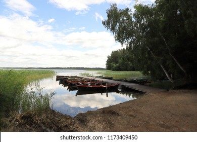 POLAND, PODLASKIE VOIVODESHIP, SUWALKI COUNTY, LAKE WIGRY - JULY 04, 2018: Lonesome rowing boats at a jetty on lake wigry