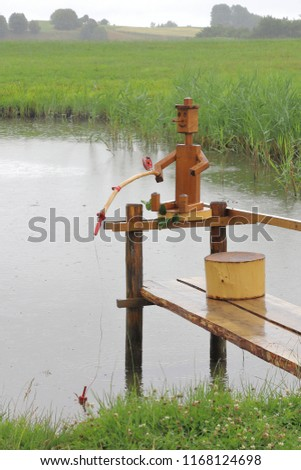 POLAND, PODLASKIE VOIVODESHIP, SUWALKI COUNTY, JODOZIORY - JULY 02, 2018: A wooden angler is fishing in the rain