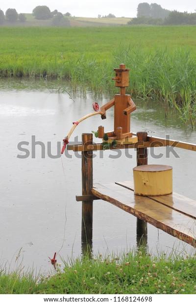 POLAND, PODLASKIE VOIVODESHIP, SUWALKI COUNTY, JODOZIORY - JULY 02, 2018: A wooden angler is fishing in the rain