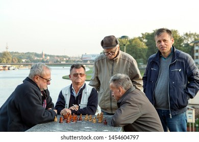 KRAKÓW / POLAND – SEPTEMBER 26 2016: Two men play at chess near river Wisla at metal chess table.