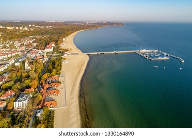 Poland, Sopot resort. Wooden pier (molo) with marina, yachts, sailboats, beach, old lighthouse, church, vacation infrastructure, hotels, park and promenade. Far view of Gdynia. Aerial view at sunrise