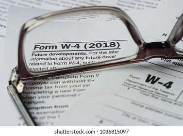 POLAND/ WARSAW - FEBRUARY 2, 2018: Glasses on the blank W-4 USA federal tax form. Training US tax legislation for those wishing to emigrate. Selective focus