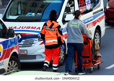 Poland, Warsaw, May 2021. Two ambulances emergency parked in the street. Paramedics are carrying a patient to a health clinic on a trolley.