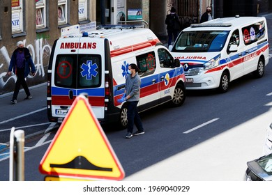 Poland, Warsaw, May 2021. Two ambulances emergency parked in the street. The paramedic opens the door of the ambulance. In the foreground a blurry road sign.