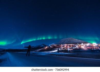 The polar arctic man Northern lights aurora borealis sky star in Norway Svalbard in Longyearbyen the moon mountains
