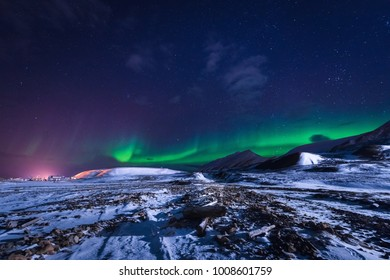The polar arctic Northern lights aurora borealis sky star in Norway Svalbard in Longyearbyen city town mountains