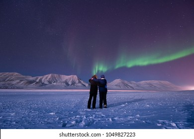 The polar arctic Northern lights aurora borealis sky star in Norway Svalbard in Longyearbyen city man people mountains