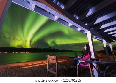 The polar arctic Northern lights aurora borealis sky star in Scandinavia Norway Tromso in the farm village  mountains with girl