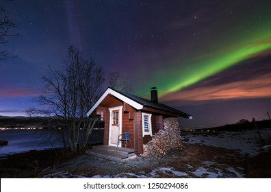 The polar arctic Northern lights aurora borealis sky star in Scandinavia Norway Tromso  mountains. Wooden house with firewood sauna in the mountains