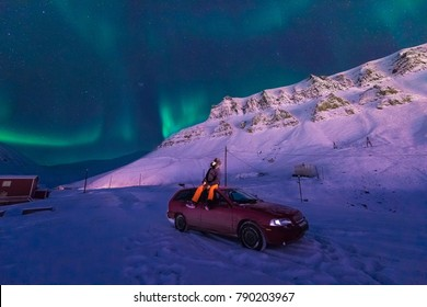 The polar arctic Northern lights aurora borealis sky star in Norway Svalbard in Longyearbyen city man car  the moon mountains