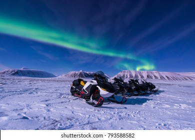 The polar arctic Northern lights aurora borealis sky star in Norway Svalbard in Longyearbyen city snowmobile the moon mountains