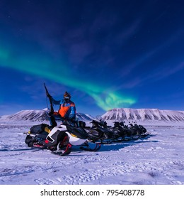 The polar arctic Northern lights aurora borealis sky star in Norway Svalbard in Longyearbyen city snowmobile man the moon mountains