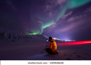 The polar arctic Northern lights hunting aurora borealis sky star in Norway travel photographer man Svalbard in Longyearbyen city the moon mountains