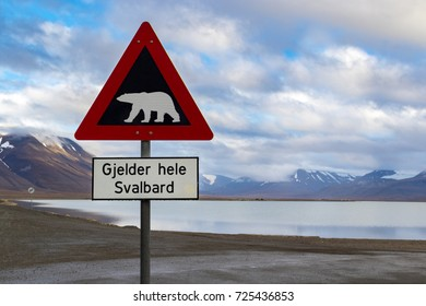 "Polar bear warning sign in Svalbard, located at the end of Longyearbyen town. Translation ""Gjelder hele Svalbard"" - valid to whole of Svalbard. Scenic view of arctic wild nature."