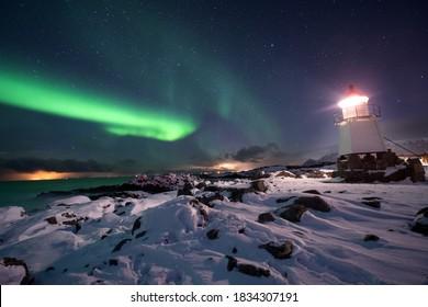 Lumière polaire pendant la nuit froide. De merveilleuses lumières dansant dans le ciel. Phare avec la lumière polaire. Soirée dans le Lofoten.