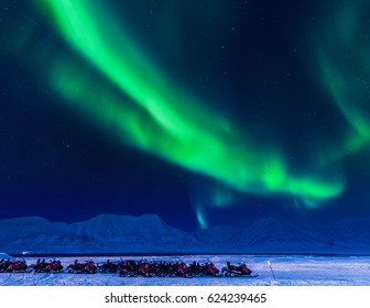 The polar Northern lights in the mountains And snowmobile of Svalbard, Longyearbyen city, Spitsbergen, Norway wallpaper