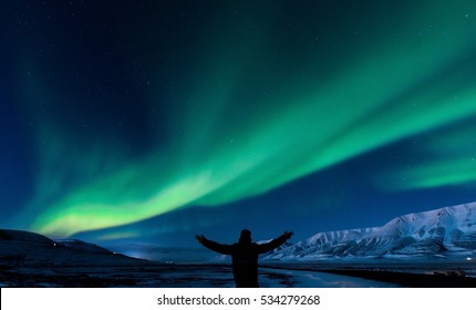 The polar Northern  lights in Norway Svalbard in the mountains  silhouette of man
