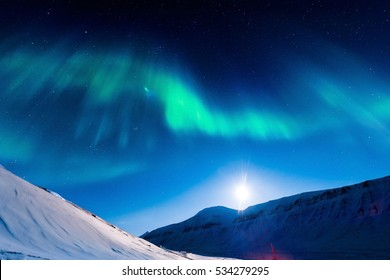 The polar Northern  lights in Norway Svalbard in the mountains moon