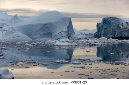 Polar regions of Earth. Icebergs of various forms and sizes. Climatic changes and growth of average annual temperature on the planet. Reduction of the area of polar ices and catastrophic thawing.