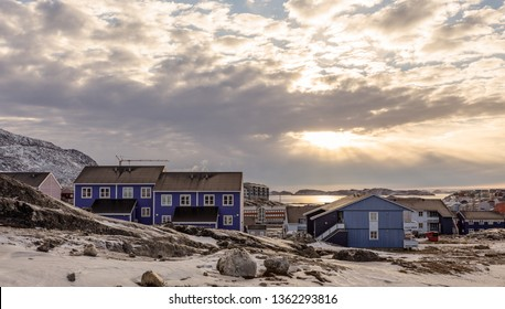 Polar sunset over Inuit houses on the rocky hills with snow, Nuuk city, Greenland