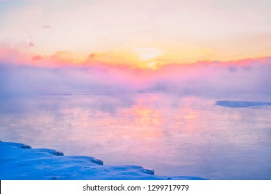 The polar vortex storms over Lake Michigan. Mist carries off the frozen lake during a beautiful, colorful sunrise.