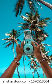 Polaroid camera and picture in a tropical place