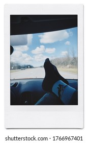 Polaroid of feet on dashboard of car on highway