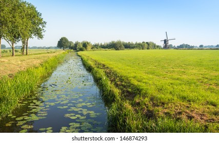 Polder landscape in the summer season with a ditch and an historic mill.